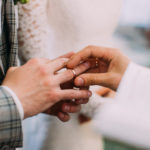 The close-up view of the priest putting the wedding ring on the finger of the groom.