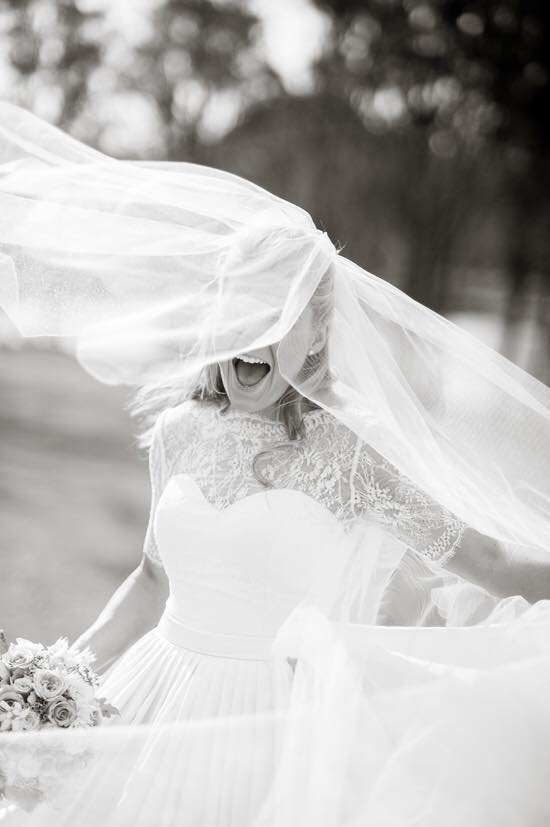 Happy bride with her veil flying over her face