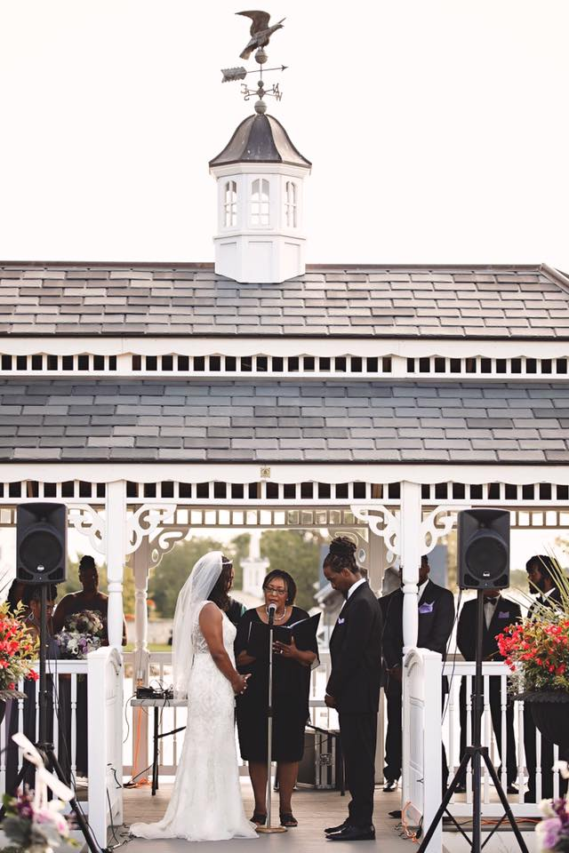 A couple getting married under a gazebo