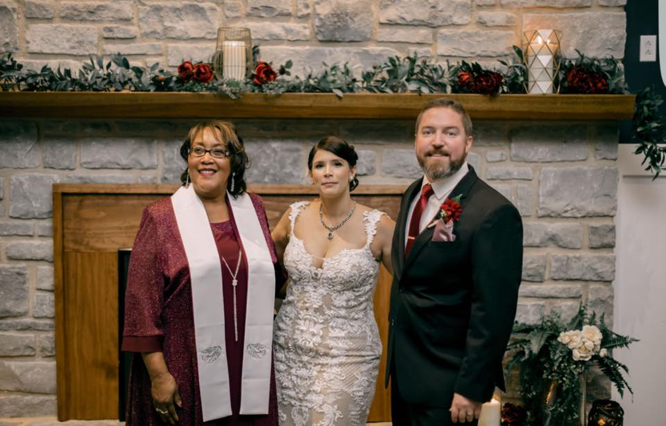 A wedding officiant posing for a picture with a just married couple