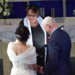 A couple reciting their vows in front of an alter